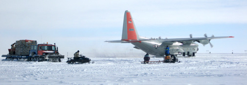 Cargo has just been rolled onto the new off-load sled and is being dragged away while the plane prepares for departure.