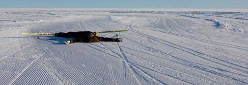 A not as skilled skier taking a rest on the skiway.